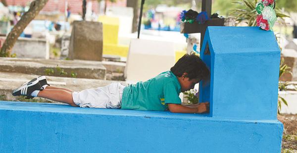 Este niño intenta colocar una vela en una de las tumbas. Anoche la gente visitó de forma masiva los diferentes cementerios de la ciudad. Grupos de rezadores, conformados principalmente por niños, se ofrecen para hacer oraciones por los difuntos