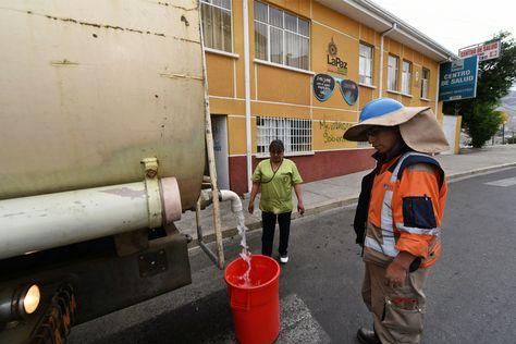 Una enfermera del centro Divino Maestro, en Alto Obrajes, recibe agua en un tacho. Foto: Miguel Carrasco