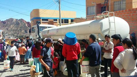 Vecinos reciben agua de un carro bombero este domingo 13 de noviembre de 2016.