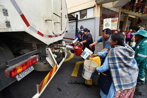Vecinos reciben agua en tachos. Foto: La Razón