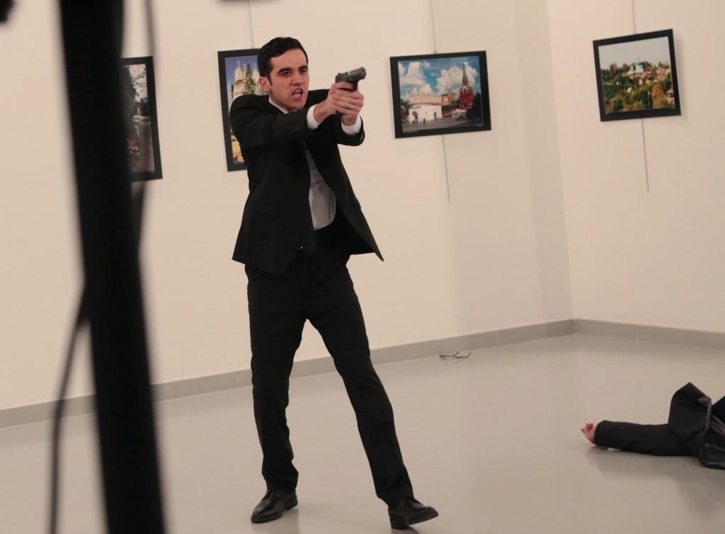 Mevlüt Mert Altintas apunta a la gente con su arma tras ejecutar al diplomático (AP Photo/Burhan Ozbilici)
