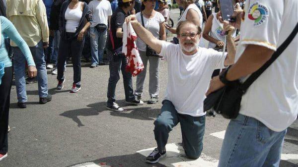 Un hombre muestra la remera ensangrentada de una víctima de la represión chavista