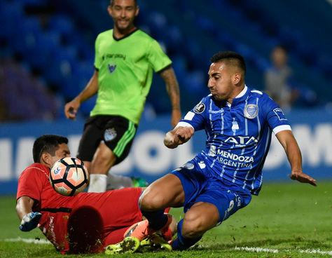 El guardameta Carlos Arias de Sport Boys choca contra el jugador argentino de Godoy Cruz Javier Correa.
