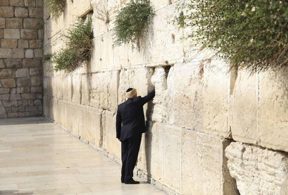 Donald Trump introducido en uno de los intersticios de los bloques de piedra un papel doblado, en un ritual en el que generalmente se expresan deseos o plegariasrn rn