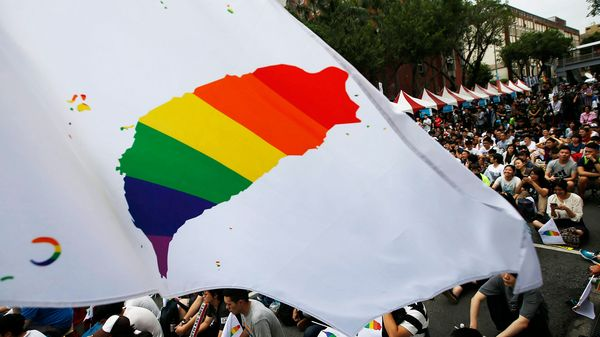 Activistas exponen la bandera simbólica de la comunidad LGBT (lesbianas, gays, bisexuales y transexuales) ante el Parlamento en Taipéi (EFE)