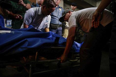 Empleados de una funeraria trasladan el cuerpo sin vida de una de las víctimas del asalto perpetrado anoche por un hombre fuertemente armado para robar un casino. Foto: EFE
