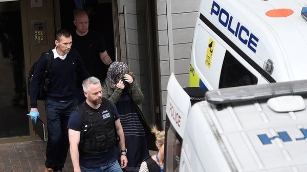 La policía escolta a una mujer luego de revisar su domicilio (Reuters)