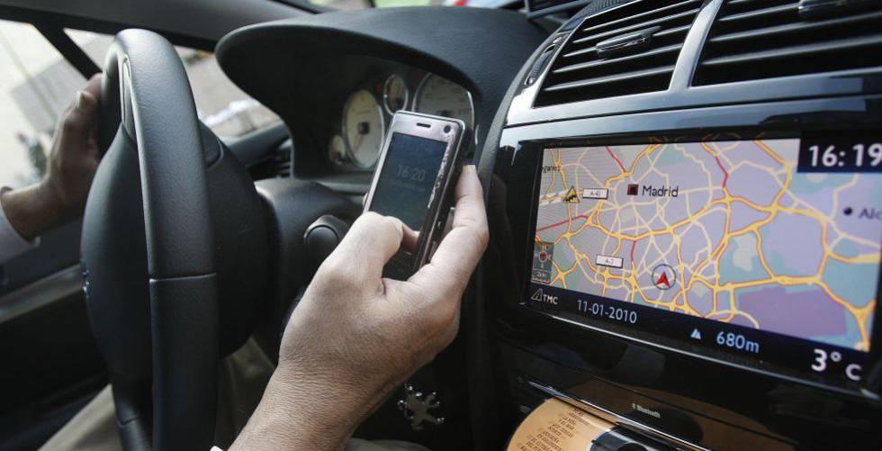 Un conductor consulta su teléfono móvil.