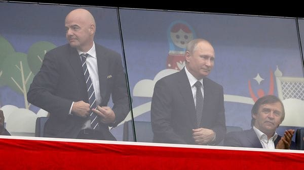 Gianni Infantino junto a Vladimir Putin, protegidos en el estadio de San Petersburgo (Reuters)