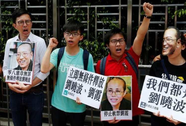 Fotos del premio Nobel Liu Xiaobo y su esposa Liu Xia durante una manifestación de disidentes en Hong Kong (Reuters)