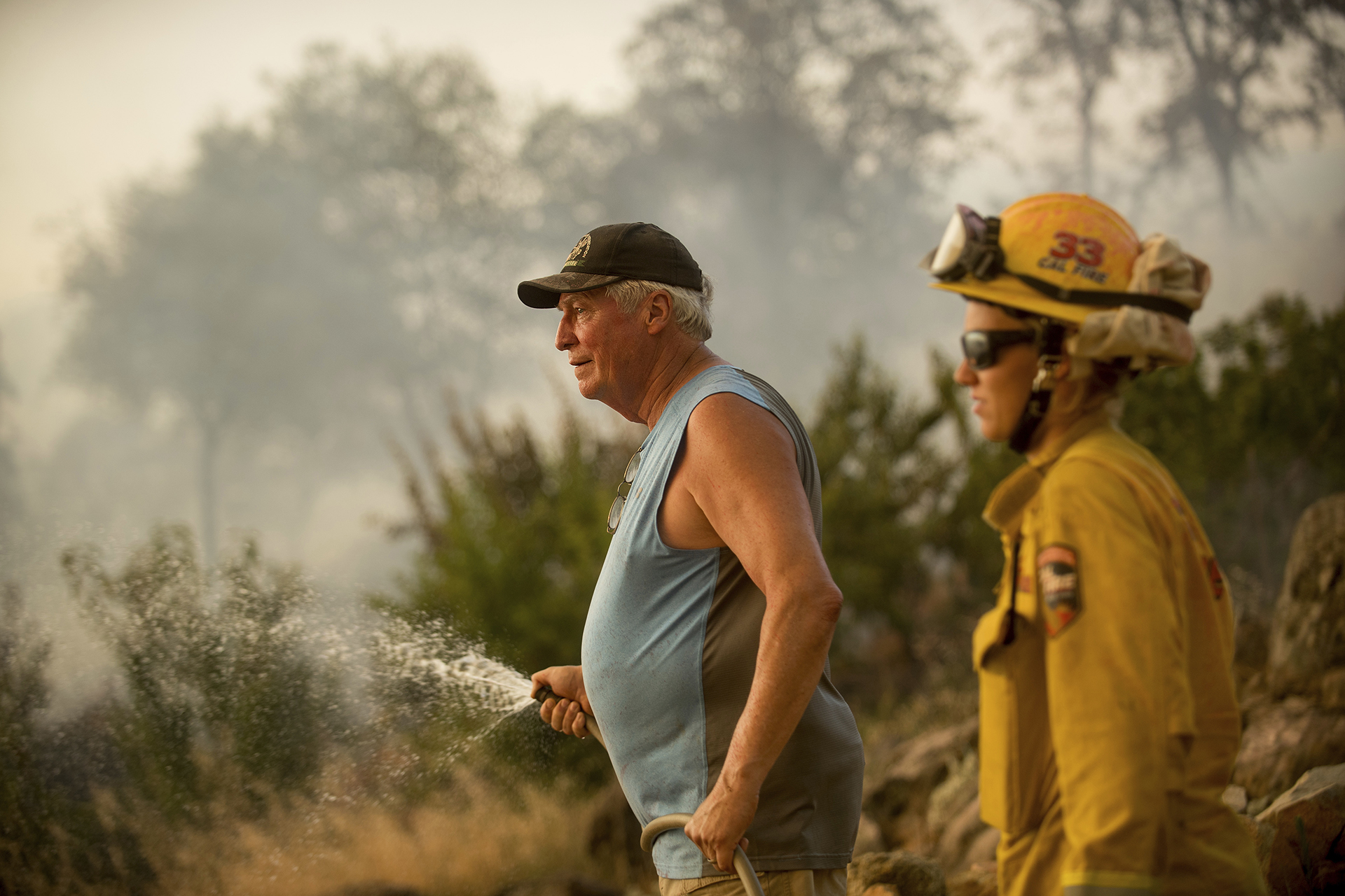 Jim Berglund esparce agua para proteger su propiedad ante el avance del fuego