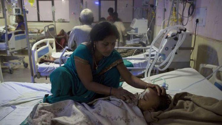 Una mujer atiende a un infante en el hospital. Más de 30 infantes murieron en tres días (AP)