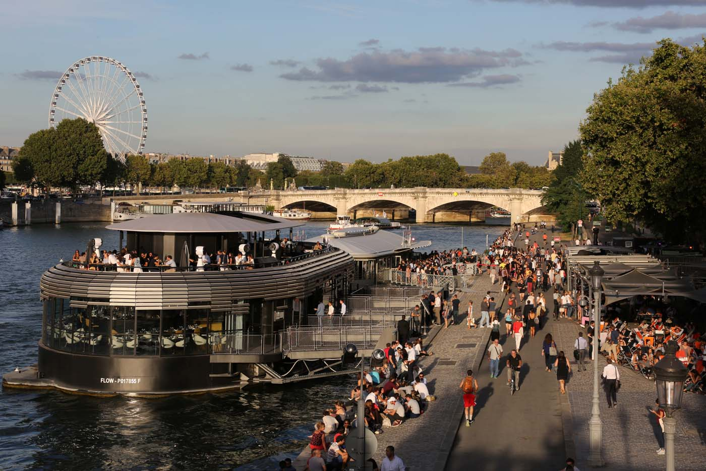 (FILES) This file photo taken on September 01, 2016 shows people having drinks near a barge on the Seine banks and the Grande Roue in Paris. After a decline in 2016 due to the terror attacks in Paris and Nice, tourism in Paris and Ile de France is in much better shape in the first half of 2017, with 1,5 million tourists and 3,3 million overnight stays more than a year ago. / AFP PHOTO / LUDOVIC MARIN