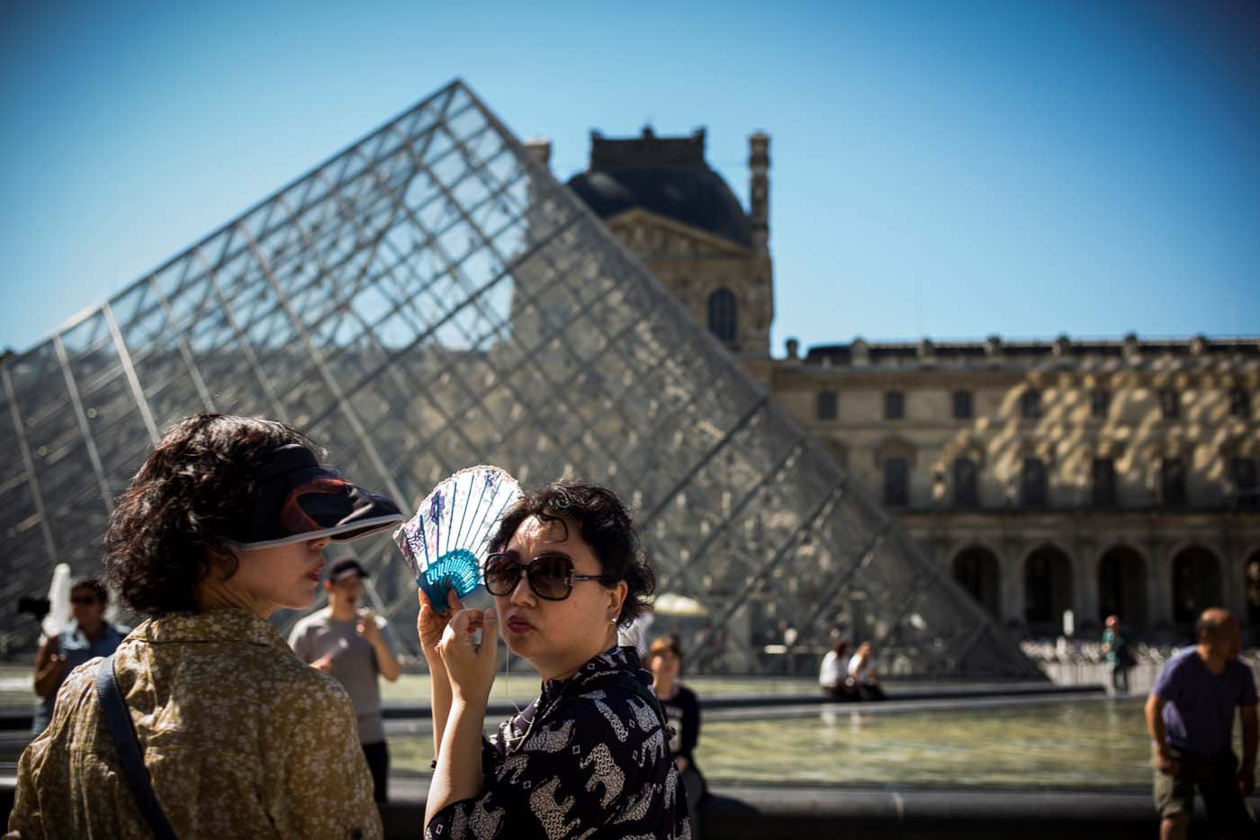 (FILES) This file photo taken on August 25, 2016 shows people standing at the Louvre museum in Paris as temperatures soar across the country. After a decline in 2016 due to the terror attacks in Paris and Nice, tourism in Paris and Ile de France is in much better shape in the first half of 2017, with 1,5 million tourists and 3,3 million overnight stays more than a year ago. / AFP PHOTO / LIONEL BONAVENTURE