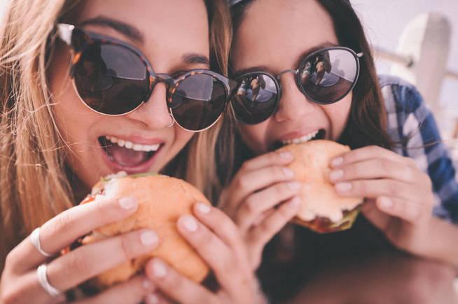 Mejores amigas adolescentes con sendas hamburguesas.