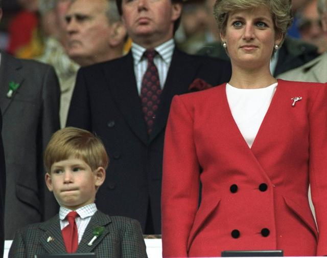 12 de octubre de 1991: Harry y Diana se levantan para escuchar el himno nacional durante un partido de fútbol.