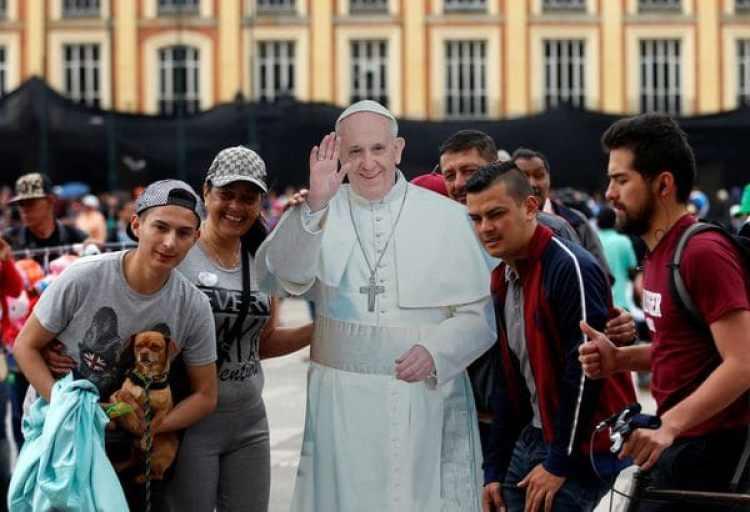 Un grupo de personas posa con un póster del papa en el centro de Bogotá. (REUTERS/Henry Romero)