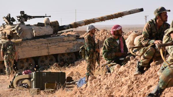 Soldados sirios apoyados por un tanque esperan para atacar
