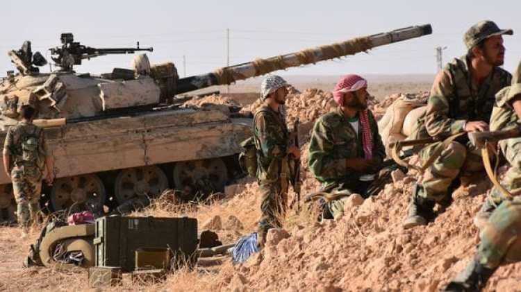 Soldados sirios apoyados por un tanque esperan para atacar (AFP)