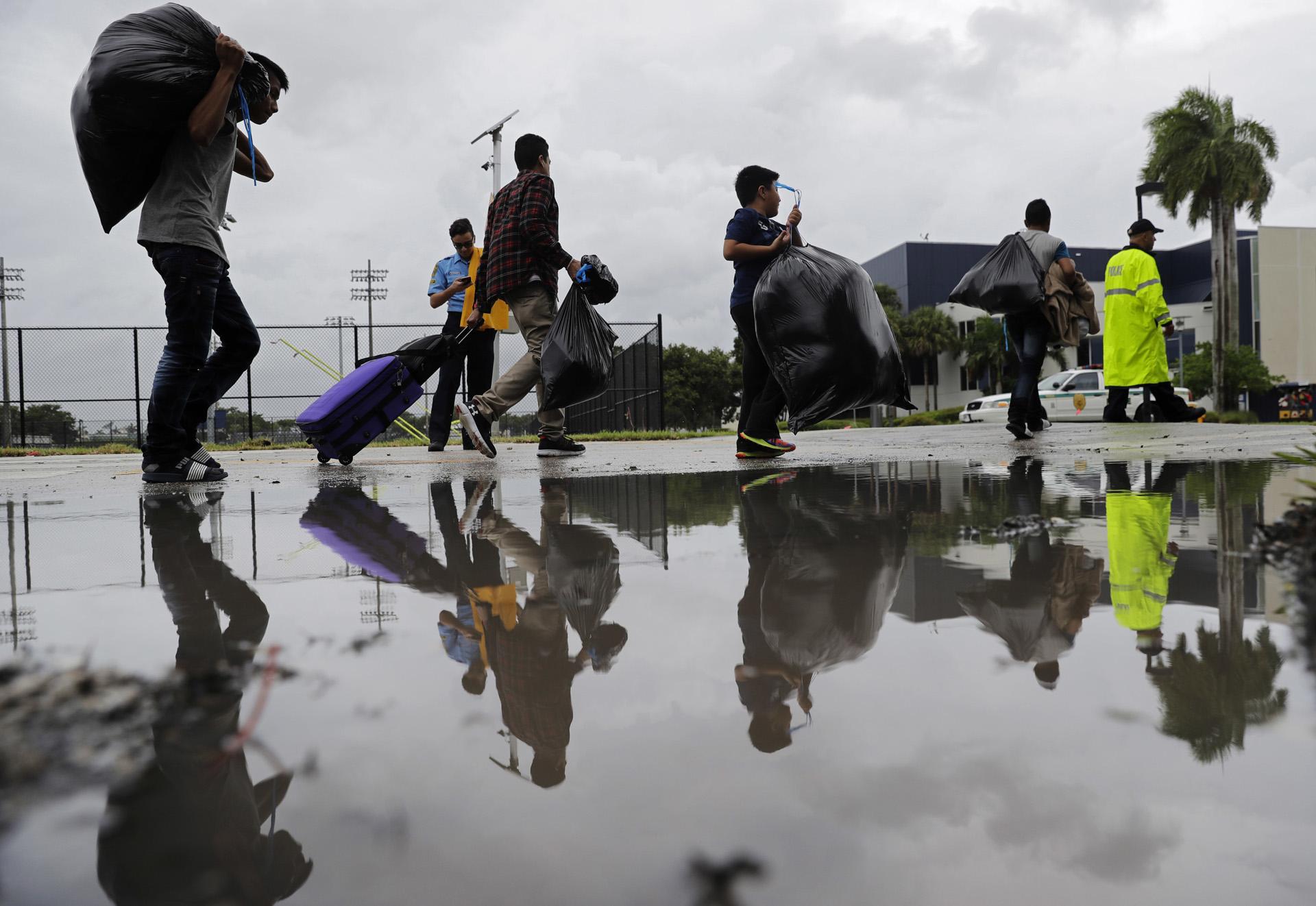 Los evacuados son trasladados a otro edificio con más baños mientras se refugian en Florida International University antes del huracán Irma en Miami. (AP)