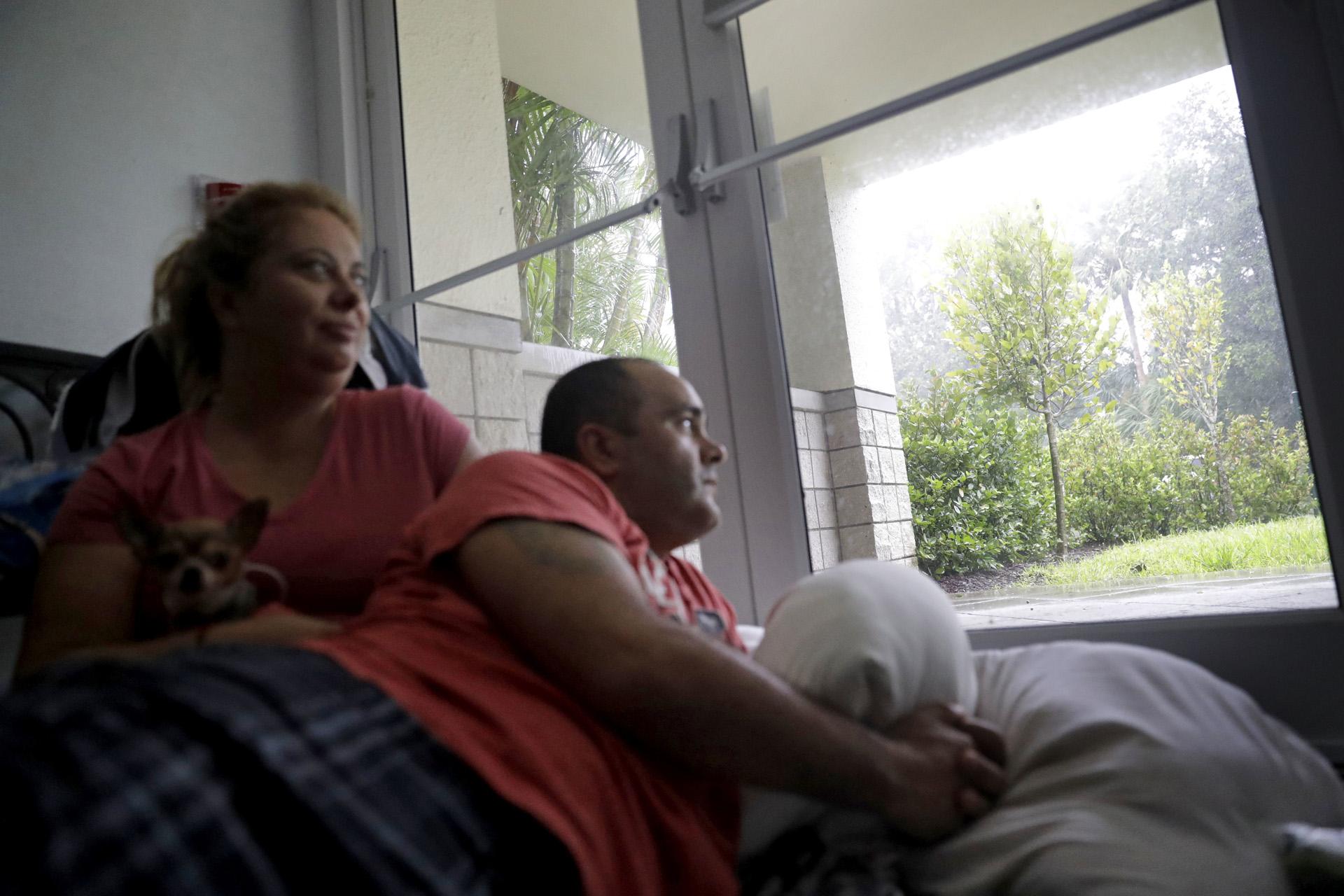 Javier García y su esposa Marissa Soto se sientan con el perro de su vecino Ilito mientras pasan el huracán Irma en un refugio en Nápoles, Florida, el domingo 10 de septiembre de 2017. (AP)