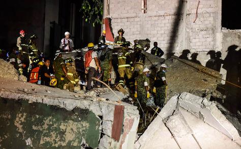 Rescatistas y personal de bomberos retiran escombros de una edificación para buscar cuerpos. Foto: AFP