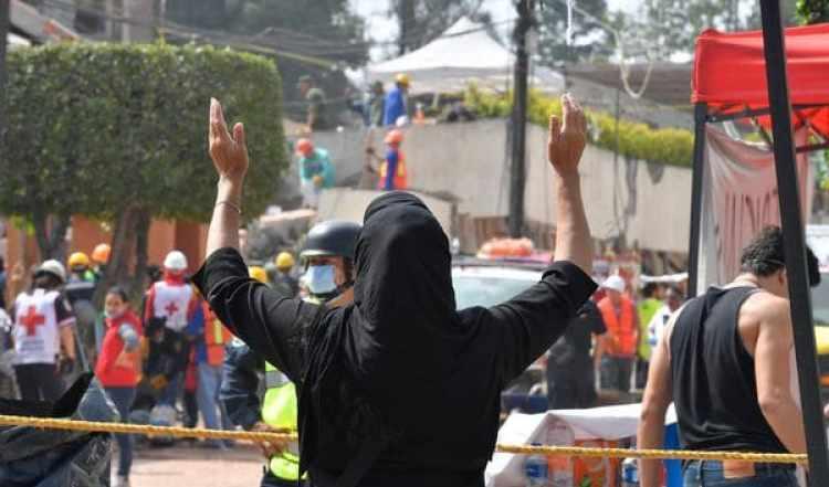 Una mujer gesticula mientras se buscan sobrevivientes en la escuela (AFP)
