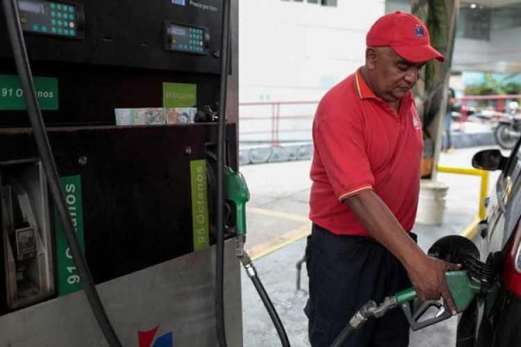 Un trabajador de una gasolinera llena el tanque de un automóvil en Caracas. (REUTERS/Marco Bello)