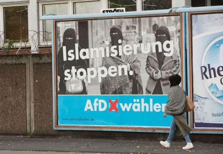 """Un mujer cubierta con el velo islámico pasa frente a un cartel de AfDque llama a """"frenar la islamización""""(Reuters)"""