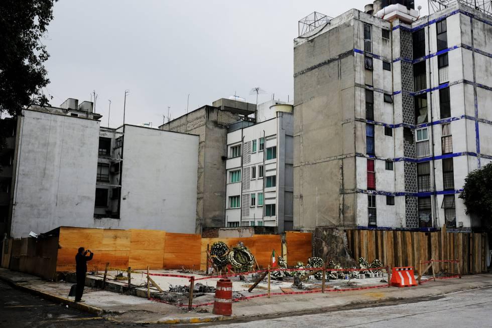 Una persona toma una fotografía en un memorial de uno de los edificios derrumbados.