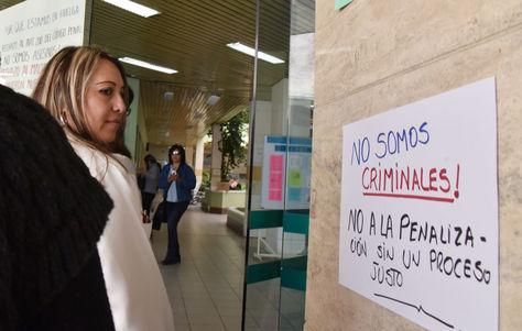 Una mujer mira uno de los letreros de protesta que pusieron los médicos al ingreso de un centro hospitalario en La Paz. Foto: José Lavayén.