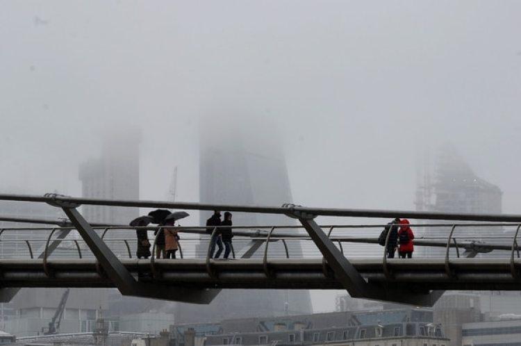 Transeúntes bajo la nieve en el Millennium Bridgede Londres(AFP)