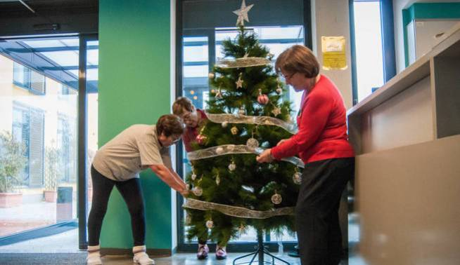 Dos residentes de Trabensol decoran un árbol de Navidad. (Carmen Castellón)