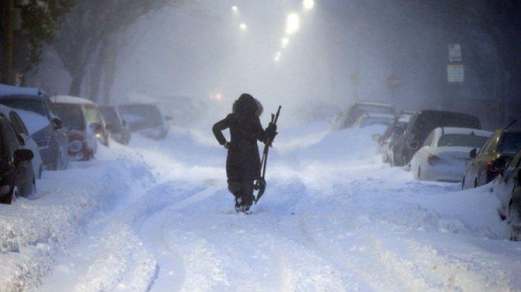 Una mujer camina en una calle de Boston durante el ciclón bomba (AP)