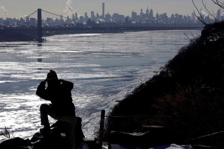 Una mujer en el Hudson River, con el puente Washington y la ciudad de Nueva York (REUTERS/Mike Segar)