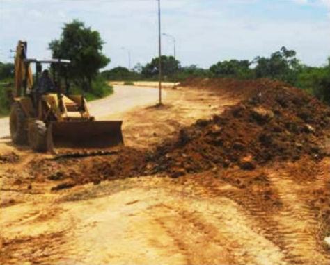 Un tractor remueve tierra para subir el nivel del terraplén que protege a Trinidad de las inundaciones.