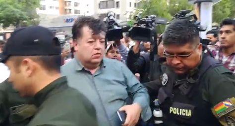 El exalcalde cochabambino es trasladado a un vehículo patrullero por efectivos policiales