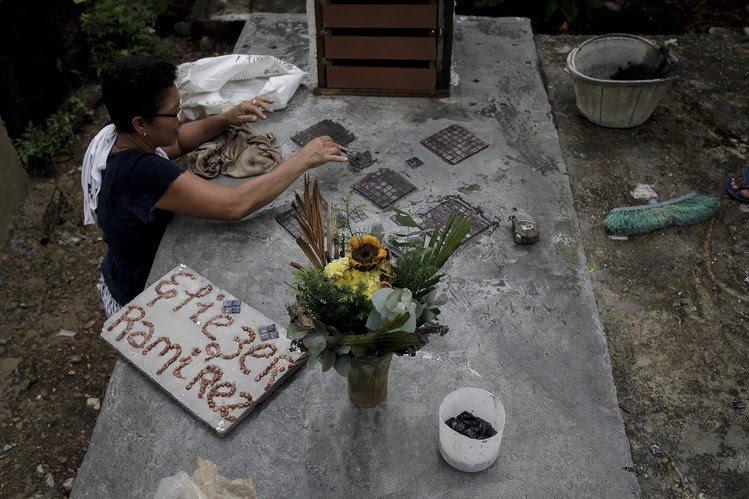 Carmen Cordero, madre de Eliezer Ramirez, decora la tumba de su hijo
