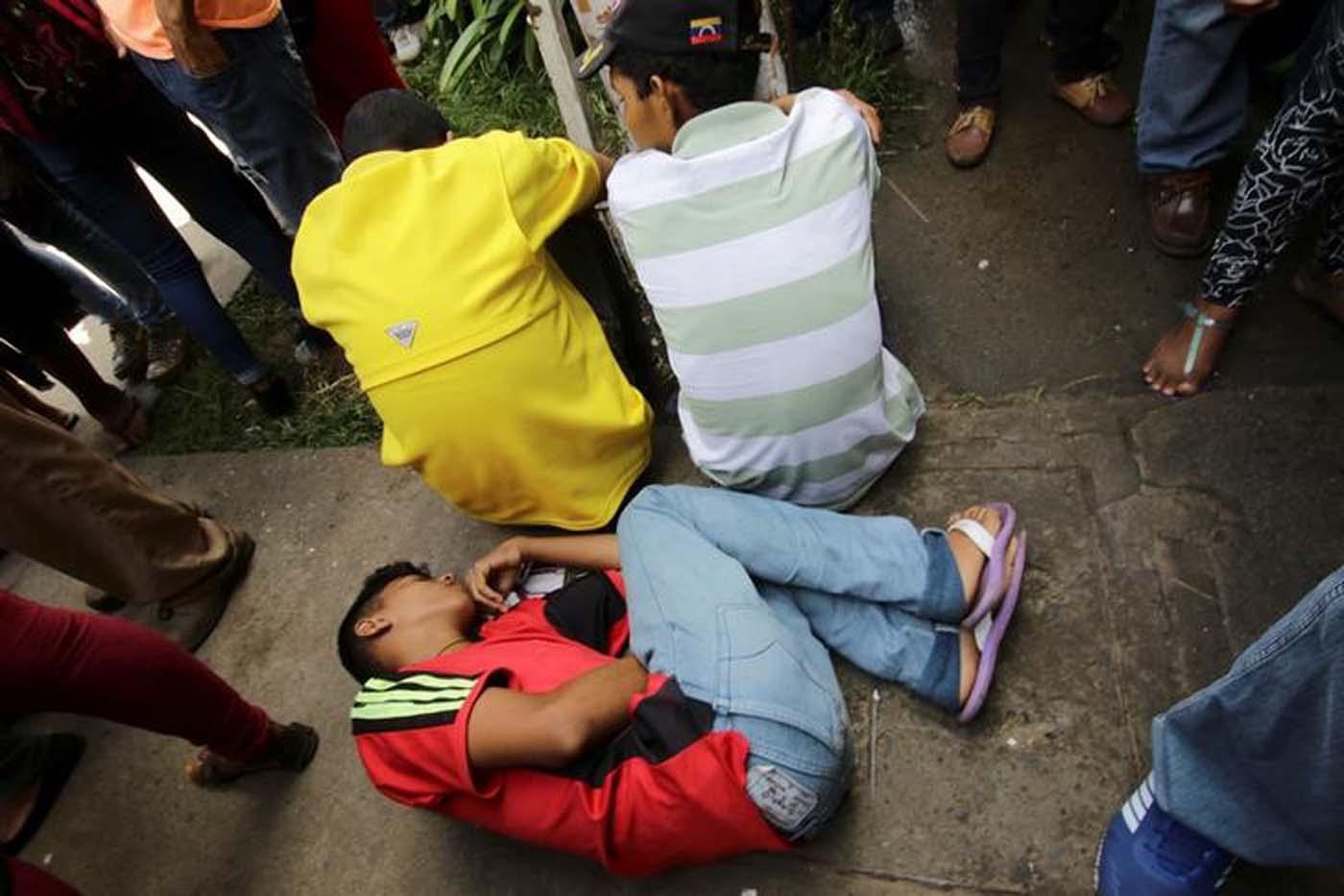 Un joven se encuentra en el piso afuera de un centro de salud mientras espera recibir tratamiento para la malaria, en San Félix, Venezuela, el 3 de noviembre de 2017. Foto tomada el 3 de noviembre de 2017. REUTERS / William Urdaneta