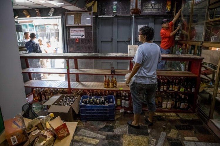 Un trabajador de una licorera saqueada el jueves 28 de diciembre de 2017 en el sector La Vega saca productos del local comercial en Caracas (EFE/MIGUEL GUTIÉRREZ)