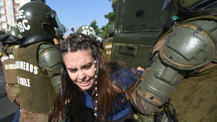 Una joven es detenida por la policía durante las protestas en Santiago. (AFP)