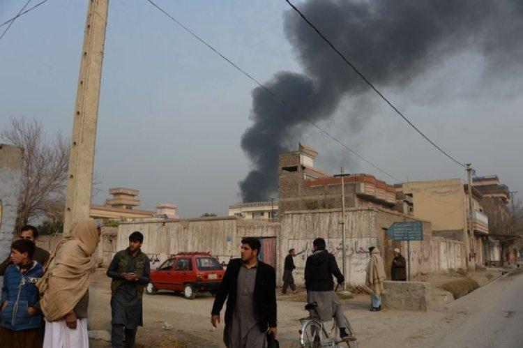Civiles afganos en Jalalabad; en el fondo se levanta el humo que proviene de la sede de Save The Children (AFP)