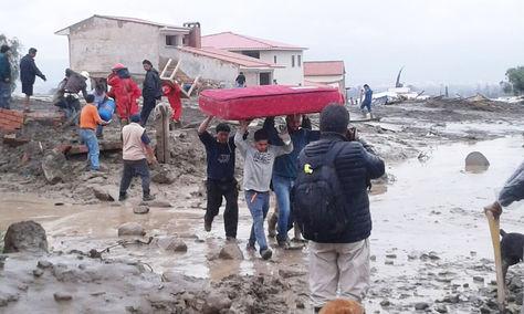 Pobladores de Tiquipaya, en una cadena humana, rescatan enseres de una vivienda enterrada en el lodo.
