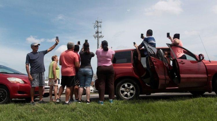 La disponibilidad de celulares sigue siendo limitada en la región, especialmente en las clases bajas. En la foto habitantes de Puerto Rico buscan señal (Reuters)