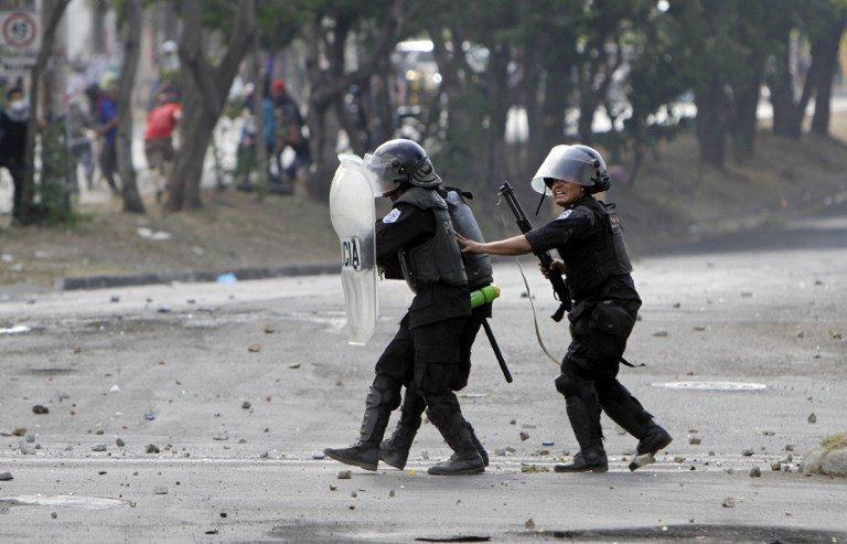 Los agentes de la policía antidisturbios se preparan para disparar durante las protestas contra las reformas del gobierno en el Instituto de Seguridad Social (INSS) en Managua el 21 de abril de 2018. AFP PHOTO / INTI OCON