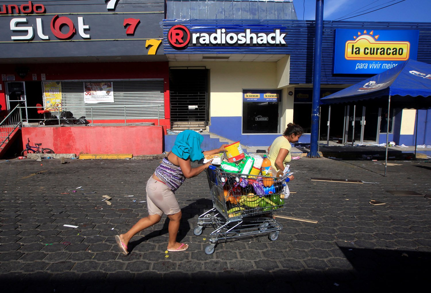 A woman with goods looted from a store walks pushing a shopping trolley along a street after protests over a reform to the pension plans of the Nicaraguan Social Security Institute (INSS) in Managua, Nicaragua April 22, 2018. REUTERS/Jorge Cabrera