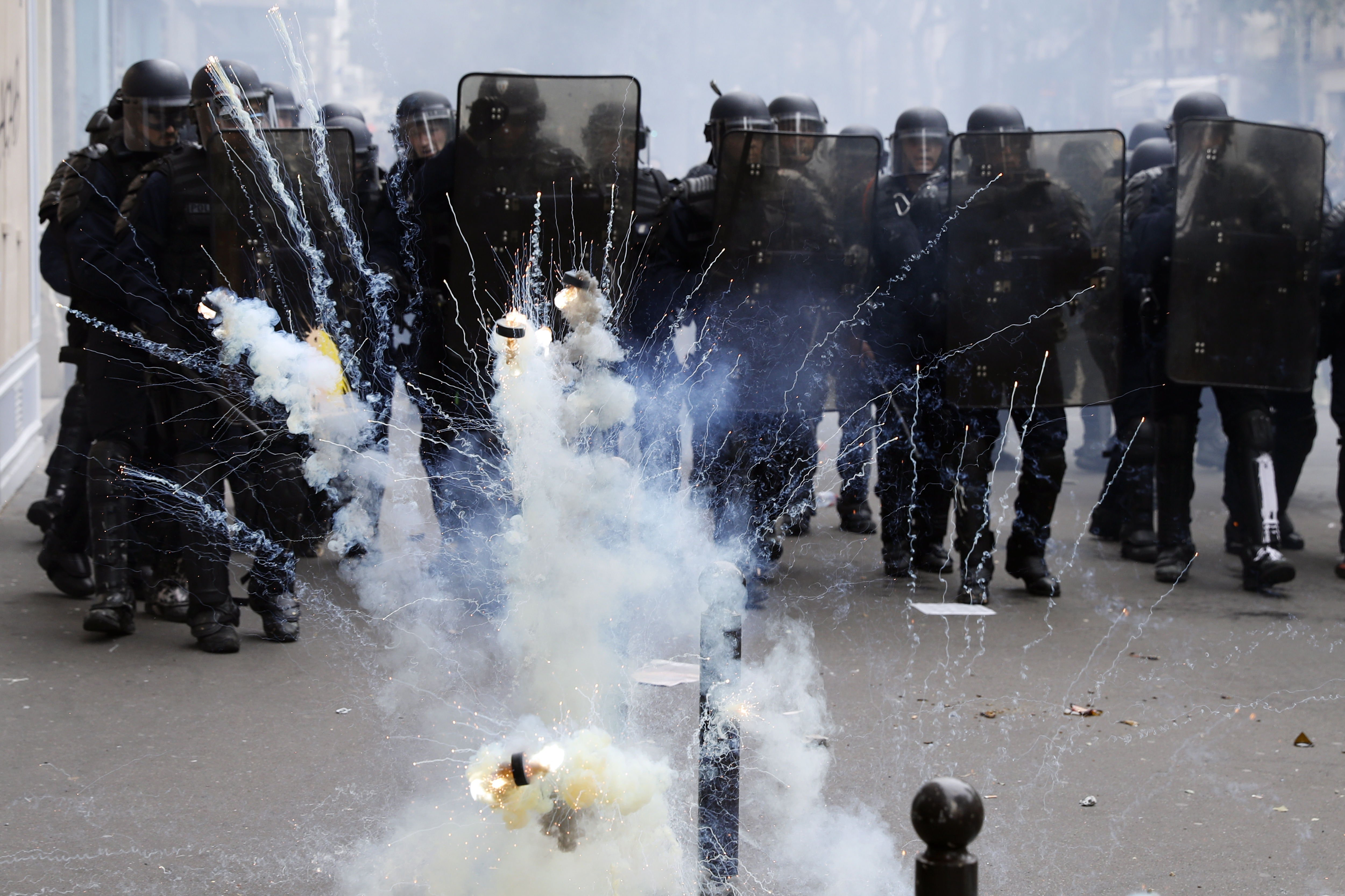Paris (France), 26/05/2018.- Tear gas palest pucks explode in front of French riot police officers during clashes with a group of protesters as thousands of people demonstrate against French government reforms in Paris, France, 26 May 2018. Far left political parties and French trade union CGT (General Confederation of Labour) call for a national day of protest against the government policies. (Protestas, Francia, Estados Unidos) EFE/EPA/ETIENNE LAURENT
