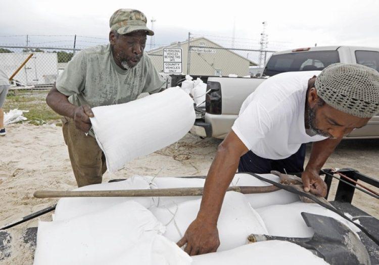 Hombres llenan bolsas de arena antes de la llegada de la tormenta (AP/Rogelio V. Solis)