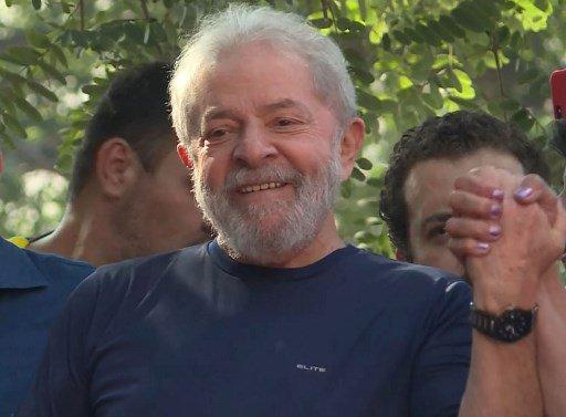 """Los partidarios del ex presidente brasileño (2003-2011) Luiz Inácio Lula da Silva sostienen pancartas que dicen """"No dejen que lo sentencien. No dejen que lo detuven"""" mientras esperan afuera del edificio sindical de los trabajadores metalúrgicos en Sao Bernardo do Campo, en el área metropolitana de Sao Paulo, Brasil, el 7 de abril de 2018. El encarcelamiento inminente del Lula de Brasil puede haber asestado un golpe devastador a la izquierda del país, pero también ha sacudido a sus rivales políticos de la derecha, la mayoría de los cuales también están siendo investigados por corrupción. Ha habido un silencio ensordecedor en torno al arresto de Luiz Inácio Lula da Silva, quien enfrenta 12 años tras las rejas por aceptar sobornos y lavado de dinero, especialmente dado que su desaparición política posiblemente elimine al principal favorito en las elecciones presidenciales de octubre.  / AFP PHOTO / Carlos Reyes"""