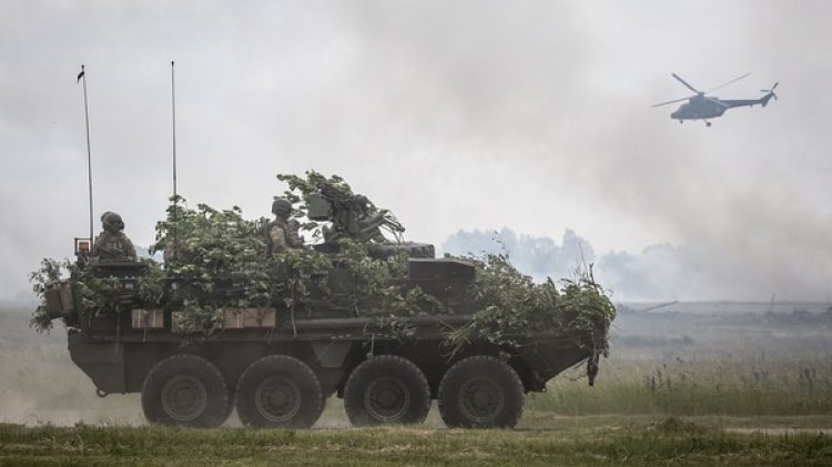 Un vehículo blindado y un helicóptero de la OTAN durante la edición de 2017 de los mismos ejercicios realizados en Polonia y los países bálticos (AFP)
